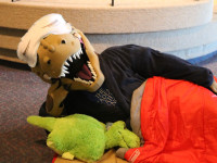 Dinosaur wearing sleep mask enjoys Night in the Museum, a fun indoor activity for families.
