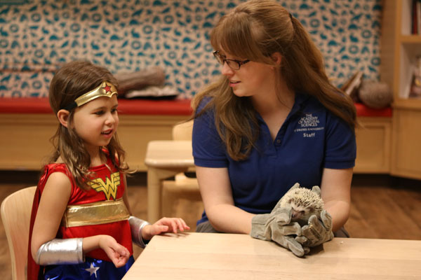 Child dressed as superhero checks out hedgehog. Early registration for summer science camp is open.