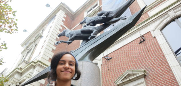 Aja Carter in front of statue at Academy of Natural Sciences