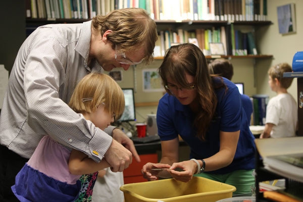 Scientist helps small child with dad do science experiment at Members night. Buy a discounted science museum membership on Cyber Monday.