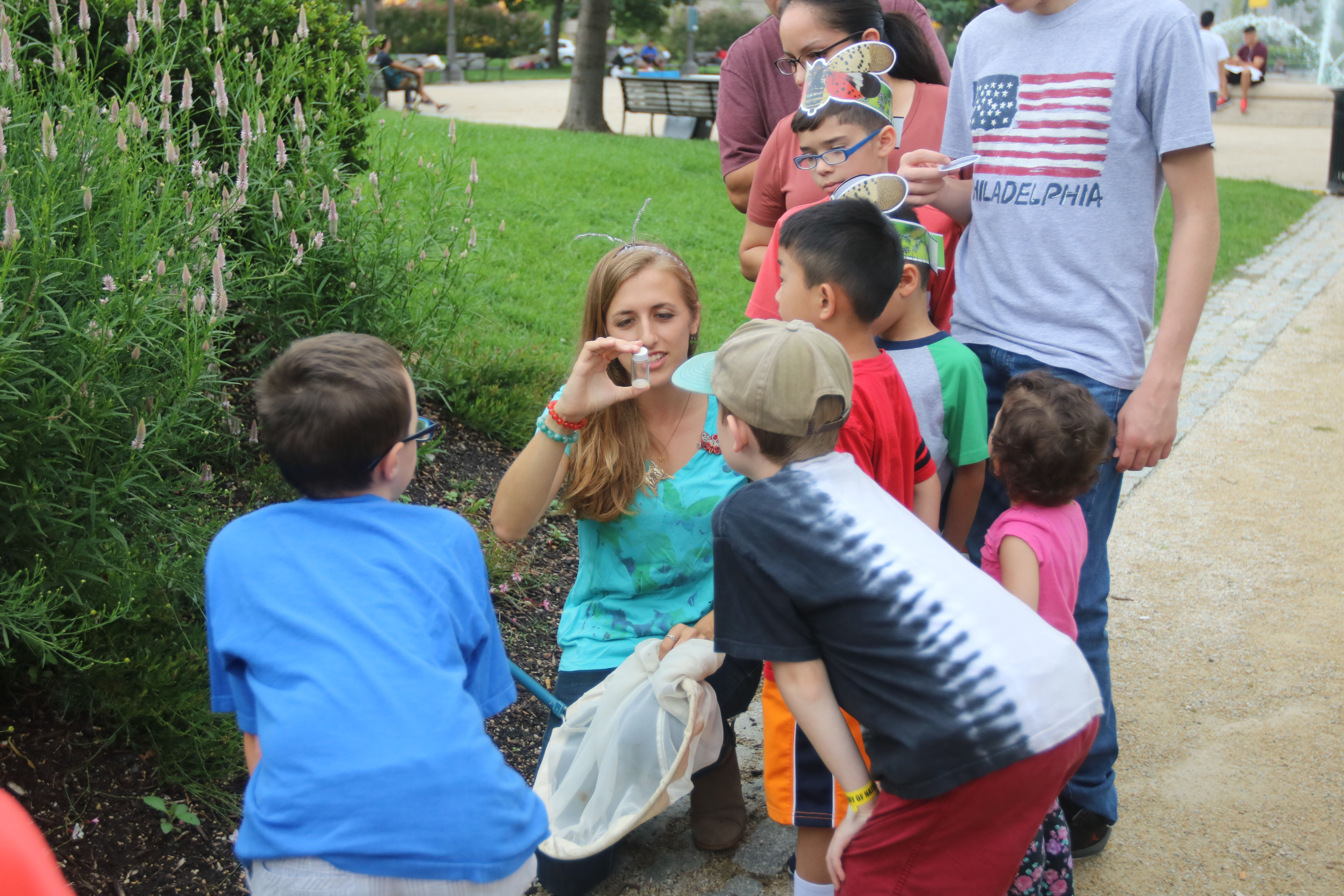 Scientist Isa Betancourt leads children on a bug walk outside the Academy of Natural Sciences