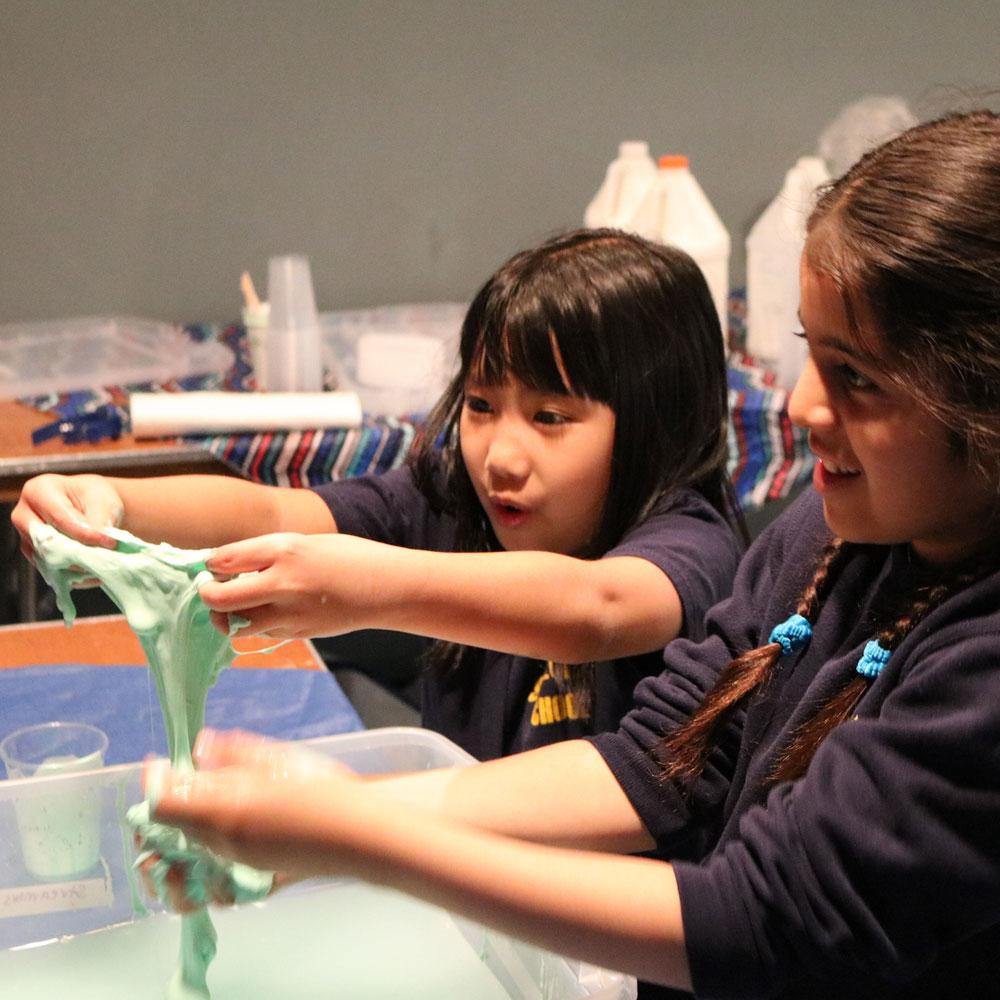 Girls making slime during dino-mite summer