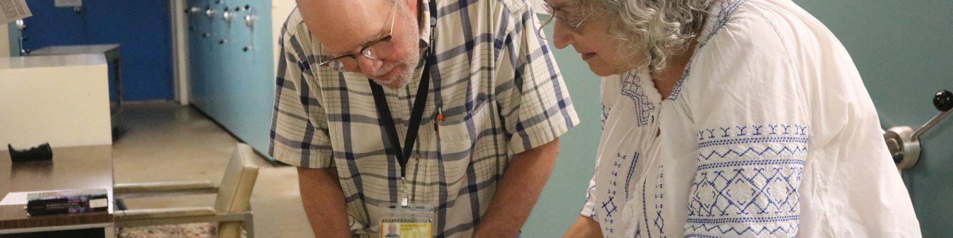 botanists examine herbarium specimen