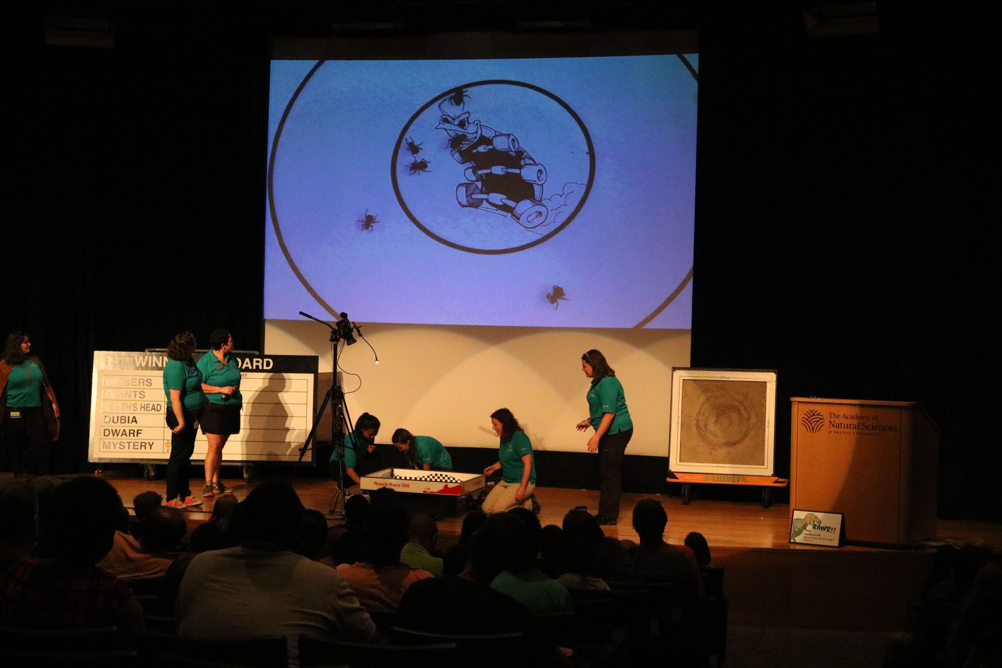 Roach race at Bug Fest. Educators on stage, bugs on big screen
