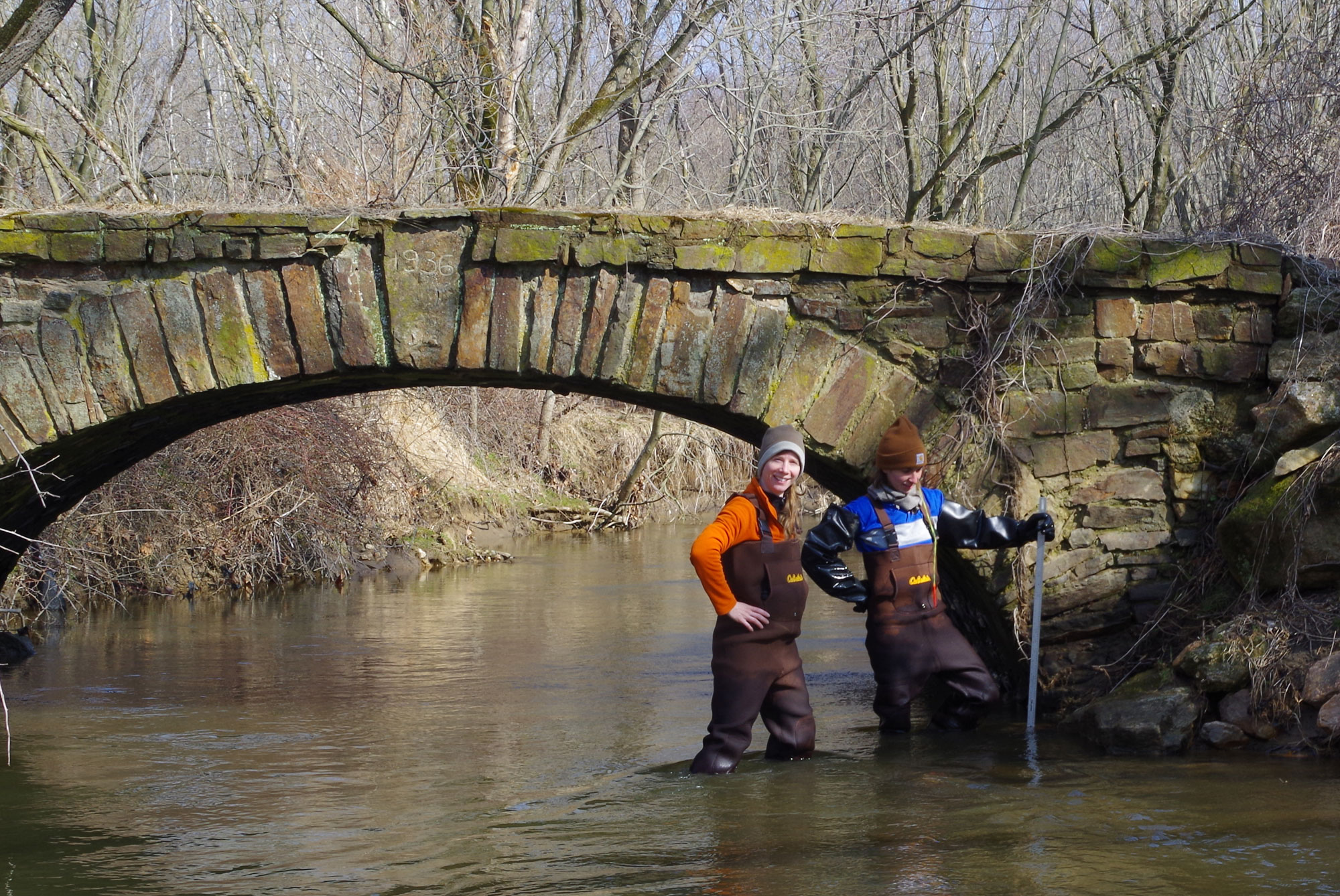 Female scientists stand knee deep in water in a stream by a bridge