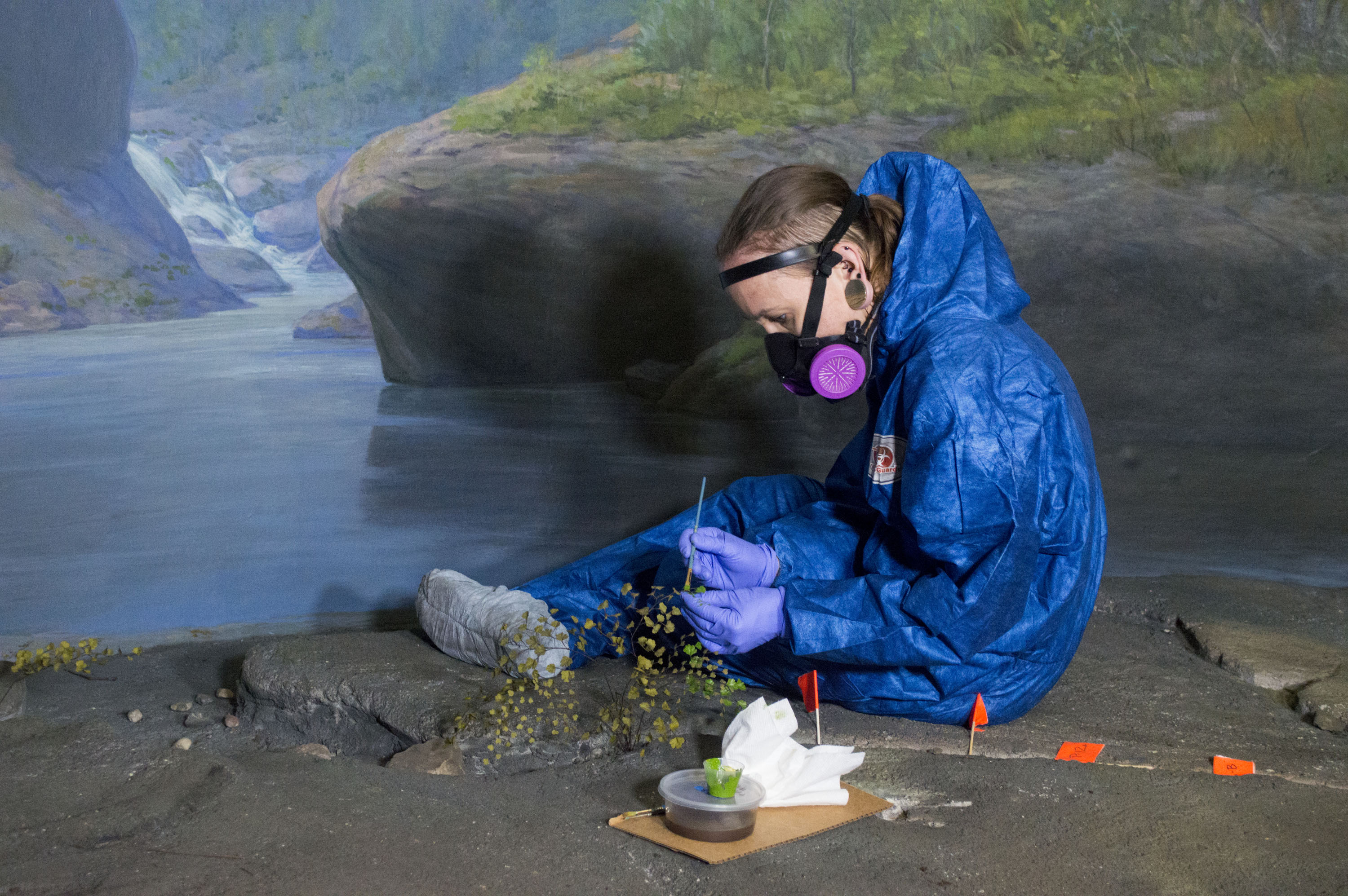 Woman in blue Tyvek suit repairs flower inside diorama