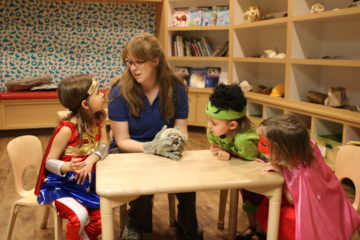 kids in costume with educator and hedgehog