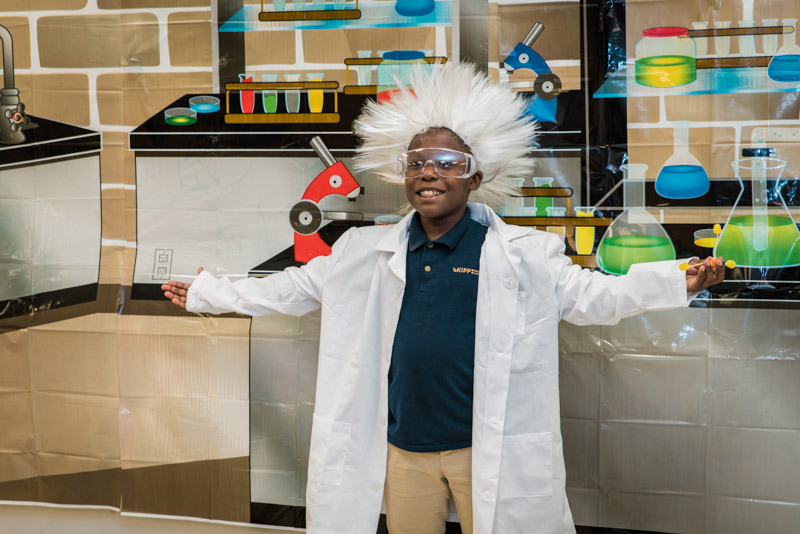 10 year old boy in lab coat and Einstein wig