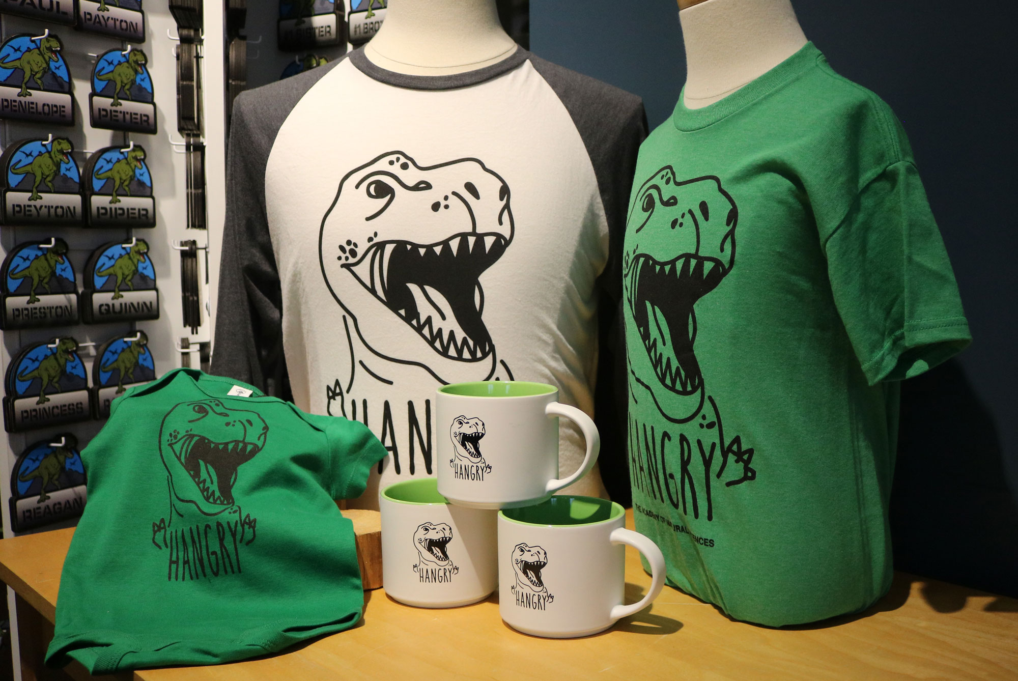 Green youth and onesie hangry shirt with T. rex, white adult baseball hangry tee, white hangry mug with T. rex with green interior