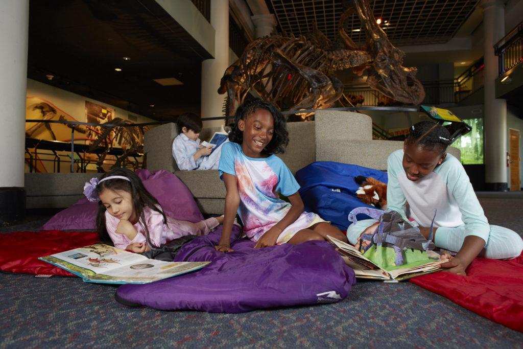 girls in sleeping bags under the T. rex