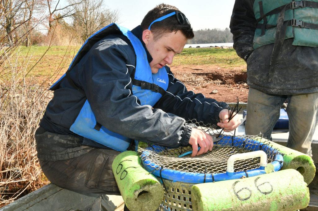 Man wearing life jacket puts netting over plastic laundry basket
