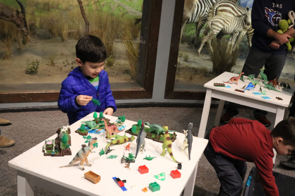 Small boy plays with legos and plastic dinosaurs at small white table