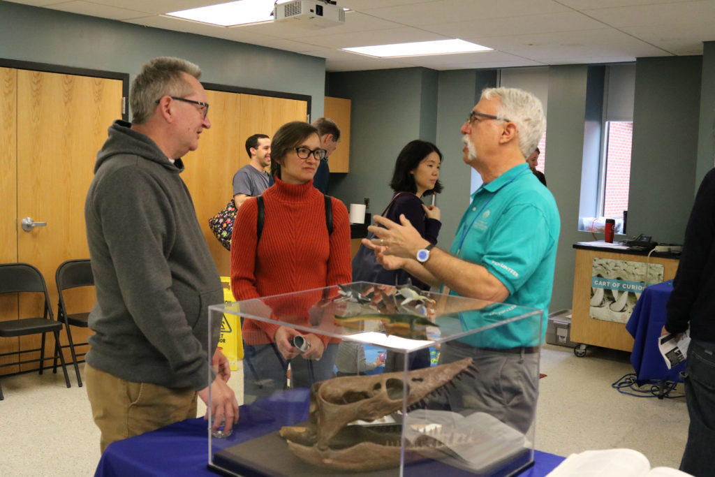 Two adults talk to Academy volunteer about marine reptile fossil in foreground