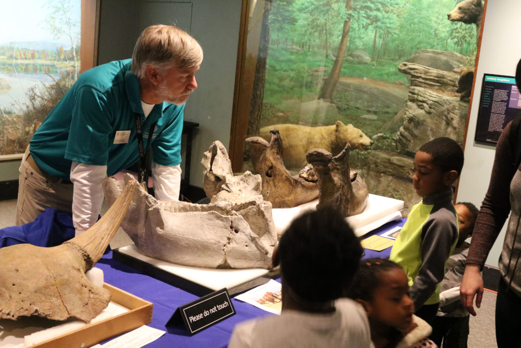 Kids under age 8 talk to male scientist about large fossils, such as a mastodon jaw, at center