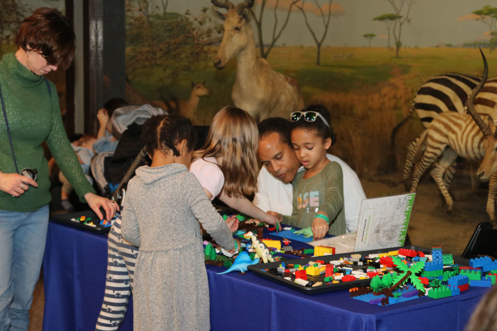 Two families play with legos and plastic dinosaurs at long table