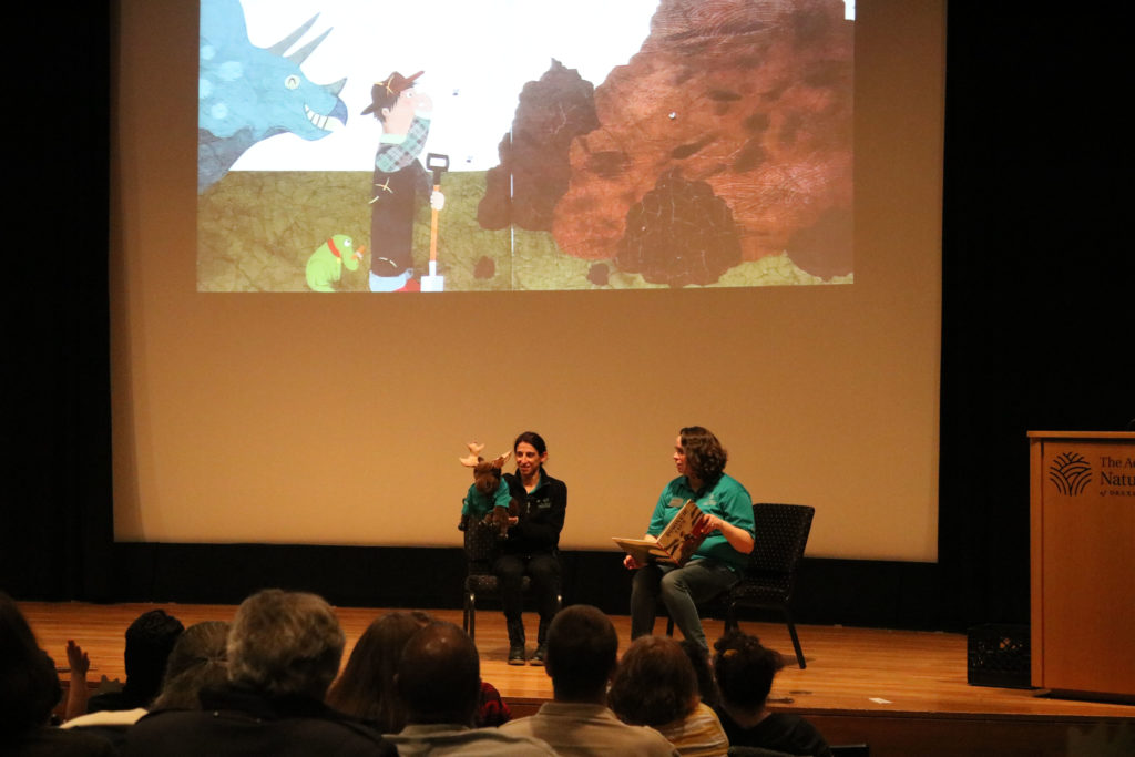 Two female educators onstage reading a story with moose puppet; story projected onscreen.
