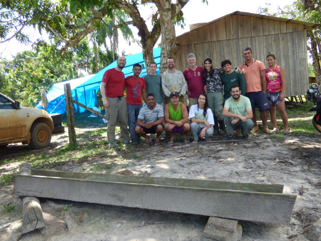 Group of scientists pose for group photo in front of wooden building