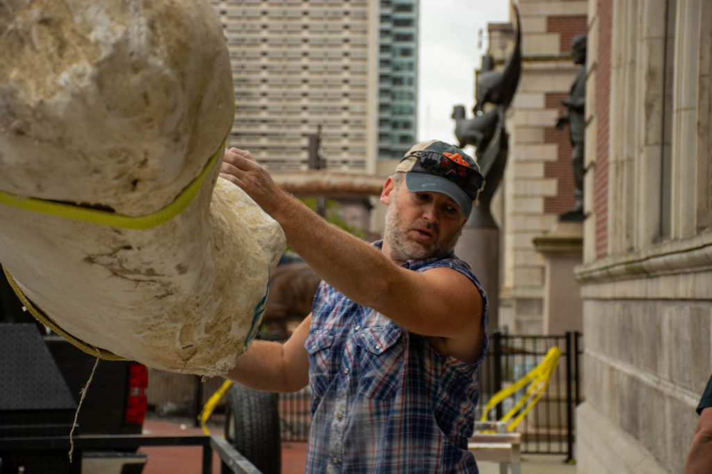 Man guides large fossil jacket off truck