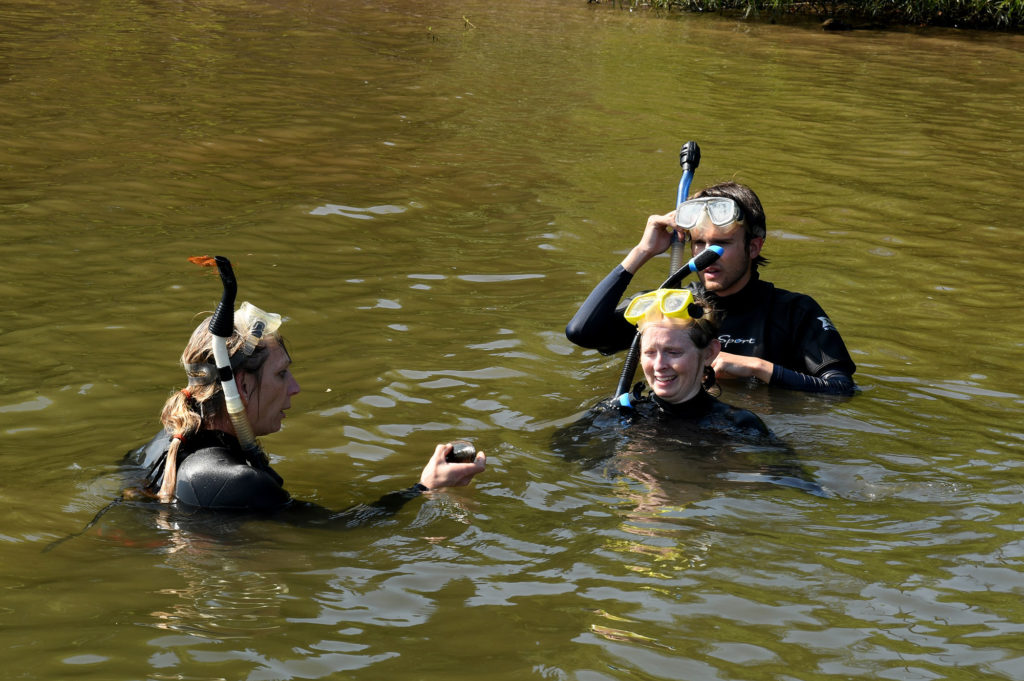 Three scientists in brownish river water