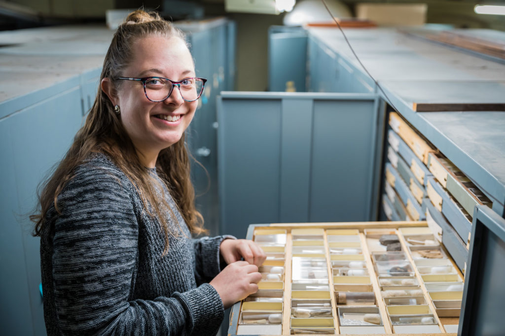 Female scientist with open drawer of invert paleo fossils