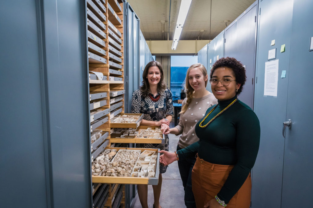 Three female scientists amidst Invert Paleo collection storage