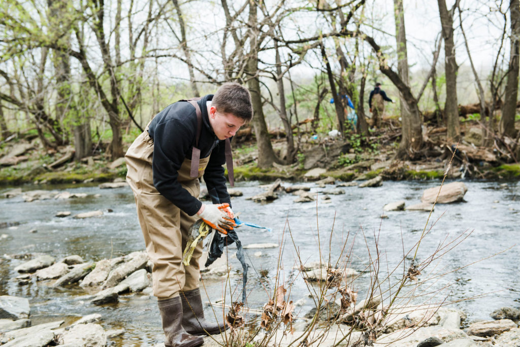 Young man picks up trash in Frankford Creek