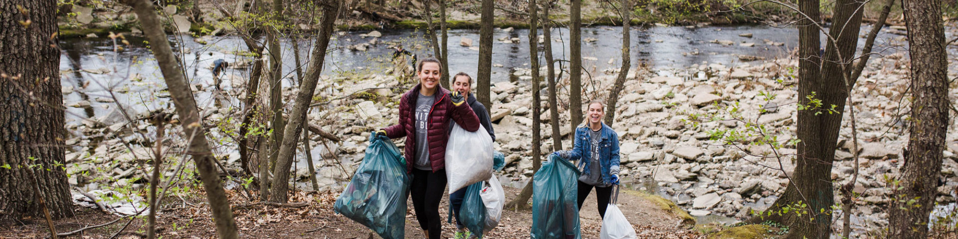Young adults carry bags of trash from Frankford Creek