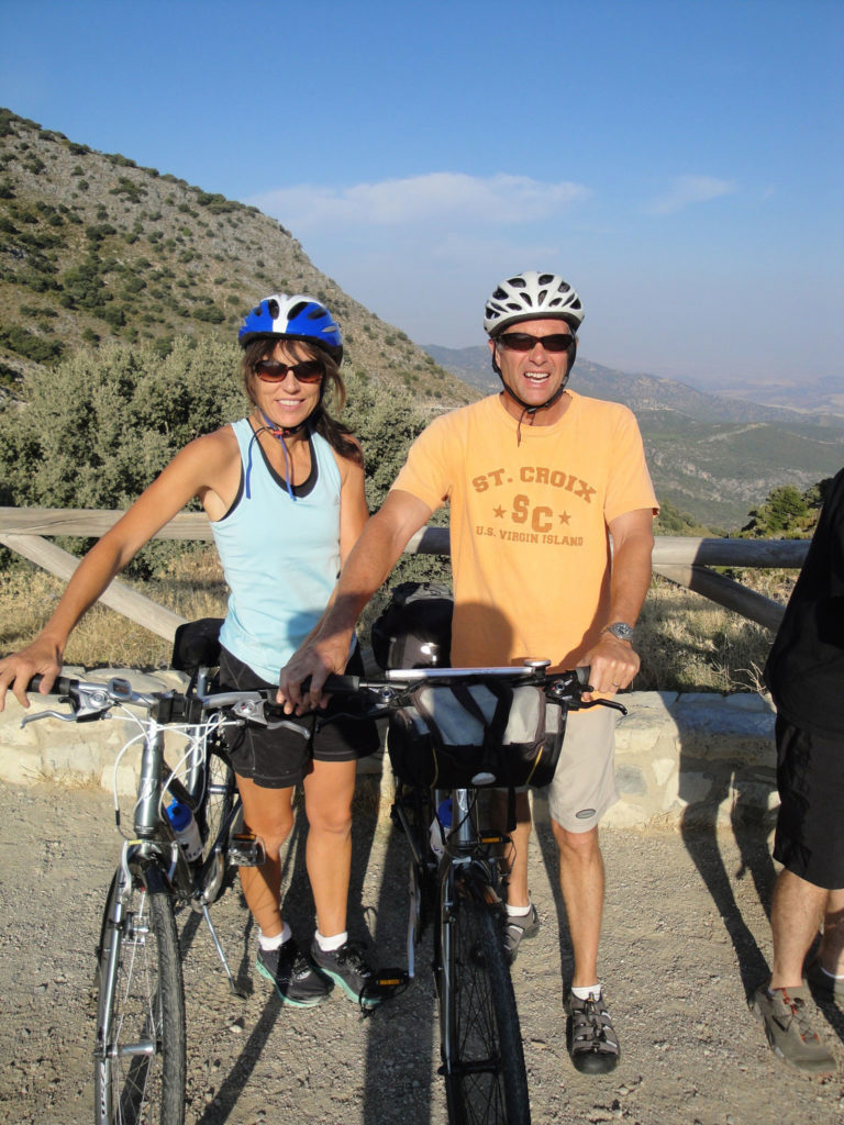 Woman and man stand beside bicycles with backdrop of mountains