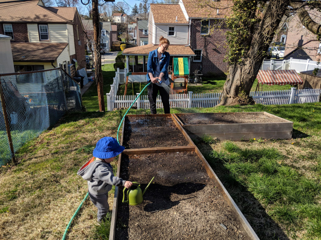 Woman and toddler water a garden bed