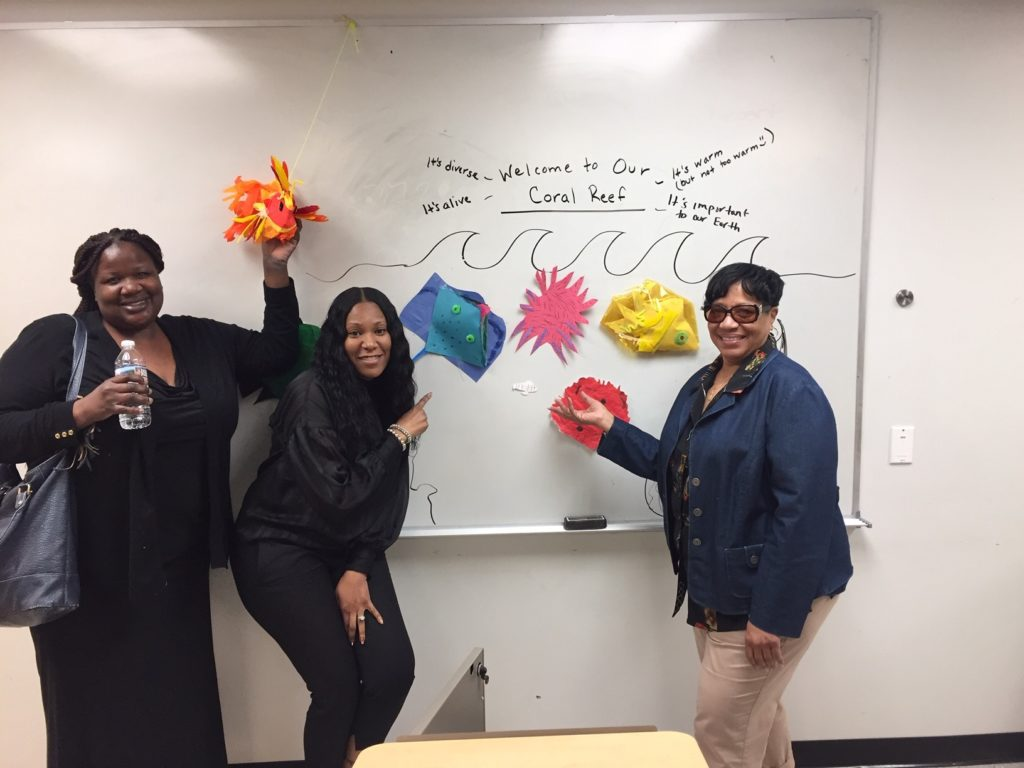 Teachers holding colorful coral reef art in front of whiteboard