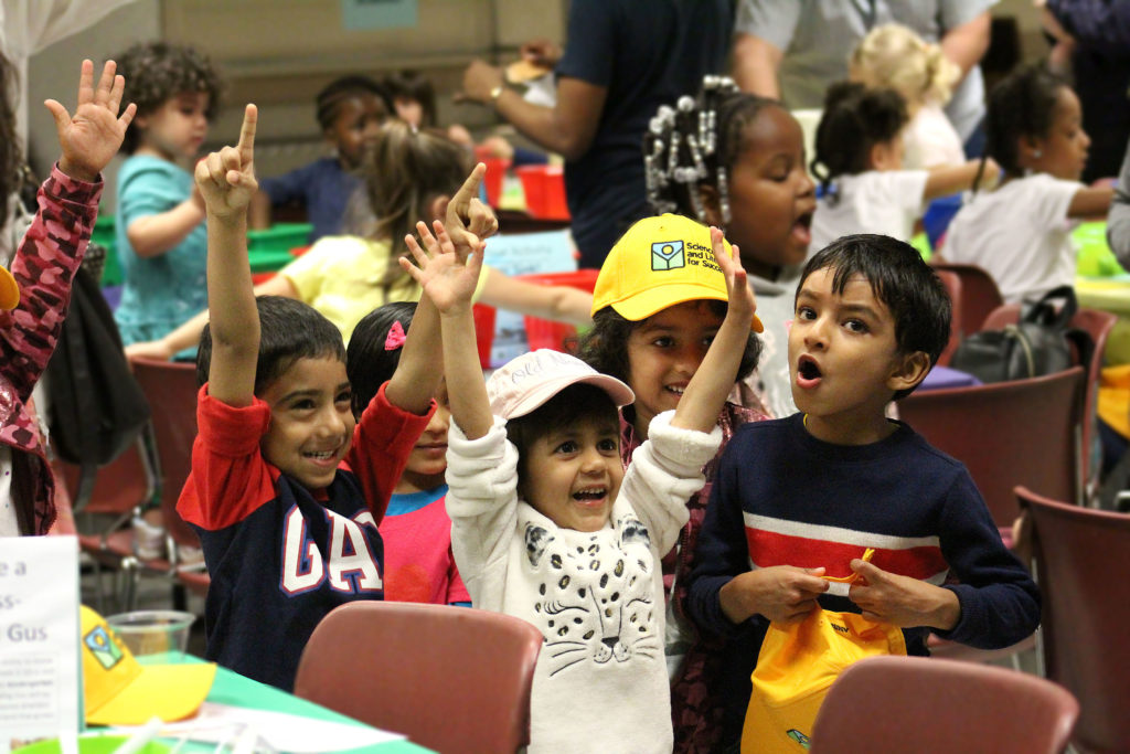 Children raise hands and smile during group activity