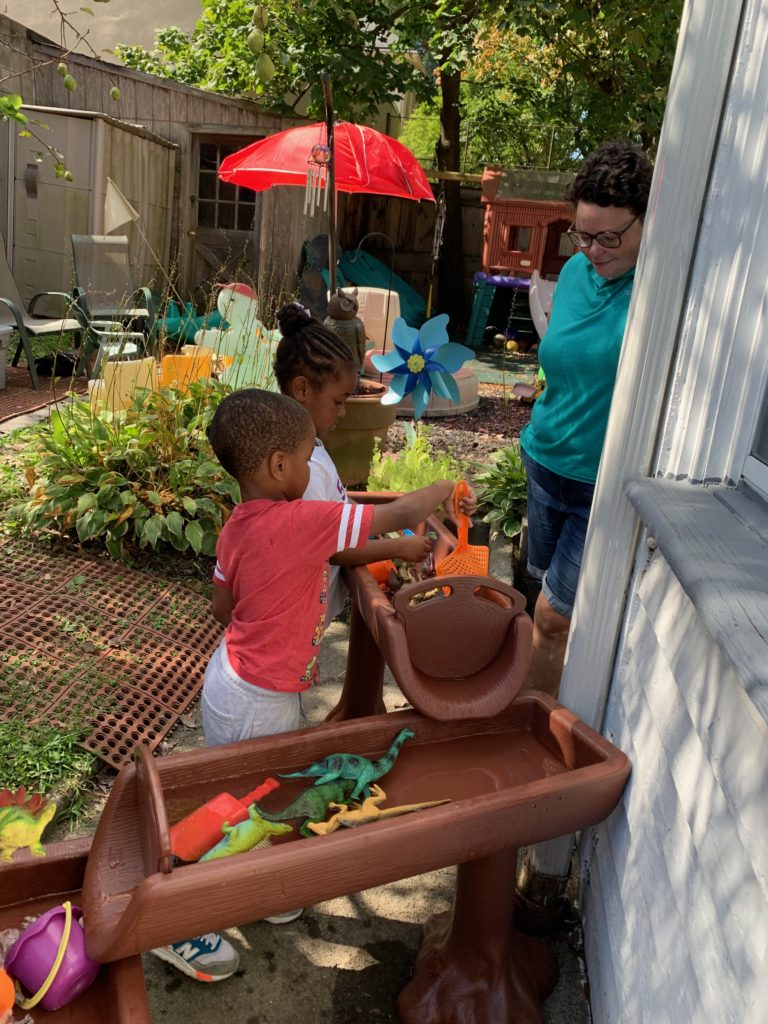 woman helps small children wash dinosaurs in colorful backyard