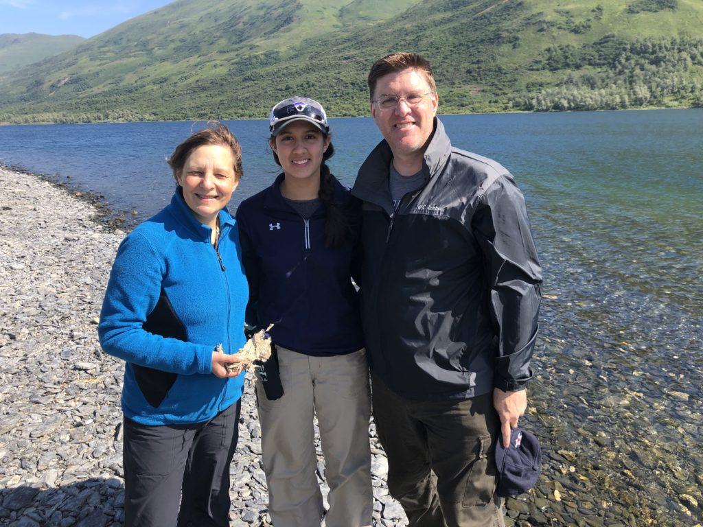 Three scientists stand beside Karluk Lake on Kodiak Island, Alaska