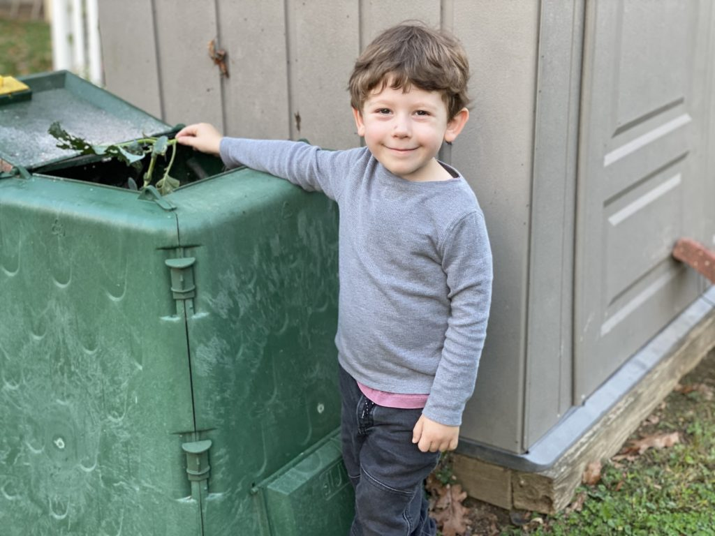 Three year old boy with brown hair, gray shirt and black pants places bird-eaten broccoli start into bright green compost bin that is almost as tall as he is