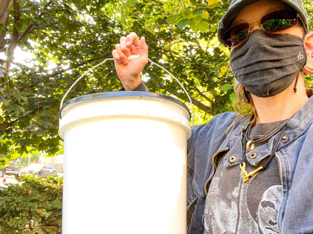 30-something adult wearing hat, sunglasses, face mask and denim jacket with gray t-shirt holds up white compost bucket against background of green treetops