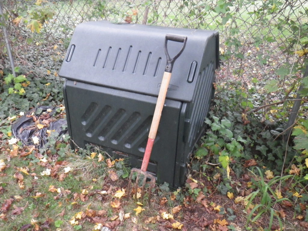 Black compost bin about three feet high with wooden handled small pitchfork leaning against it, up against a chain link fence with greens growing on it