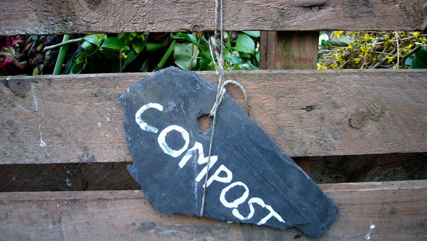 outside of wooden compost bin with black chalk sign with the word compost written on it in white