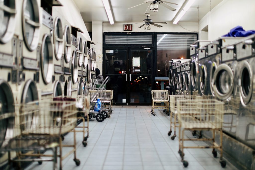 Empty laundromat with white tile floor, open laundry carts and silver machines, looking out toward the exit at nighttime