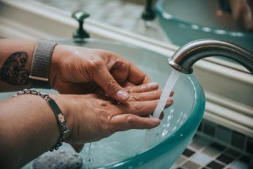 Hands being washed under running water over blue glass sink