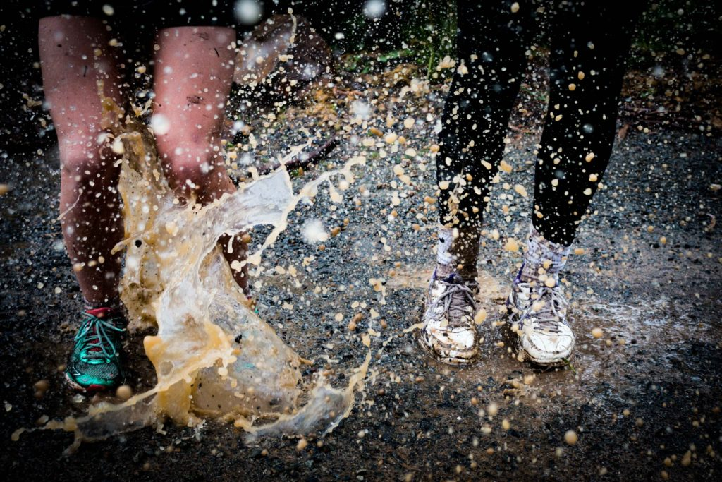 Two people splashing in muddy puddle. One wears shorts and teal sneakers, the other wears black leggings, white socks and white sneakers