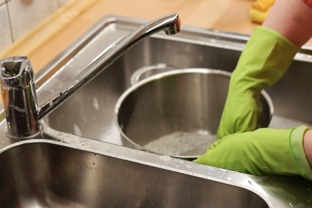 Person in neon green gloves washing large stainless steel pot in metal sink