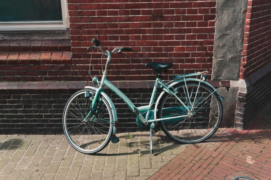 Robin's egg blue old fashioned bicycle with black seat and white kickstand leans against a brick building
