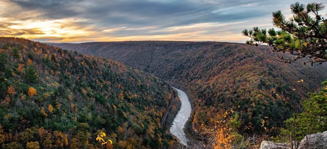vista looking over river with red and orange fall foliage